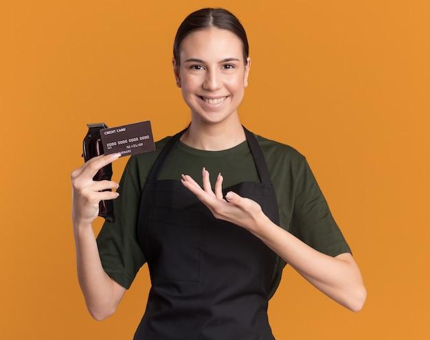 Uśmiechnięta młoda brunetka fryzjer dziewczyna w mundurze trzyma i wskazuje na maszynki do strzyżenia włosów i kartę kredytową na pomarańczowo