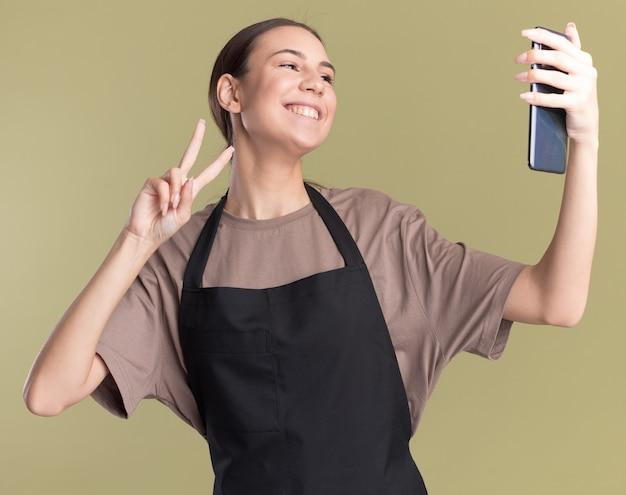 Uśmiechnięta młoda brunetka fryzjerka w mundurze gestykuluje znak zwycięstwa, patrząc na telefon, biorąc selfie