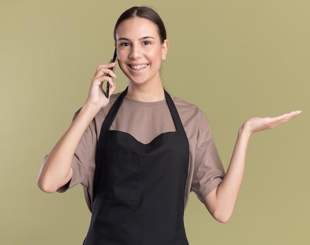 Uśmiechnięta młoda brunetka fryzjerka w mundurze trzyma rękę otwartą i rozmawia przez telefon