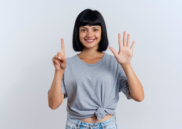 Uśmiechnięta młoda brunetka kaukaska dziewczyna gestykuluje sześć z palcami patrzeć