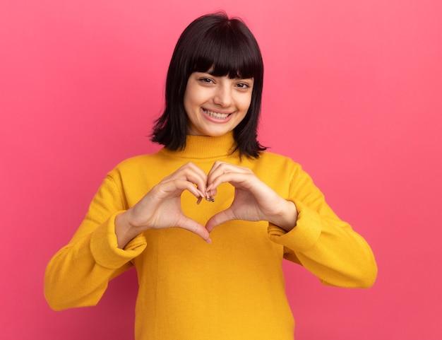 Uśmiechnięta młoda brunetka kaukaska dziewczyna gestykuluje znak serca