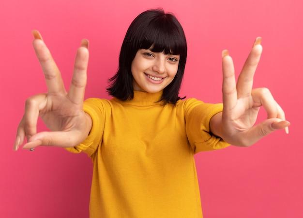 Uśmiechnięta młoda brunetka kaukaska dziewczyna gestykuluje znak zwycięstwa na różowo