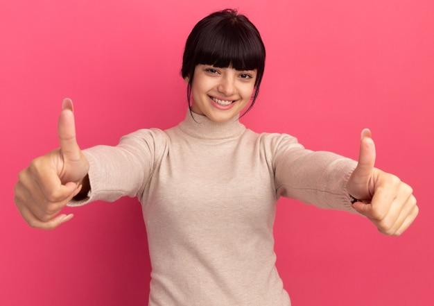 Uśmiechnięta młoda brunetka kaukaska dziewczyna kciuki z dwiema rękami na różowo