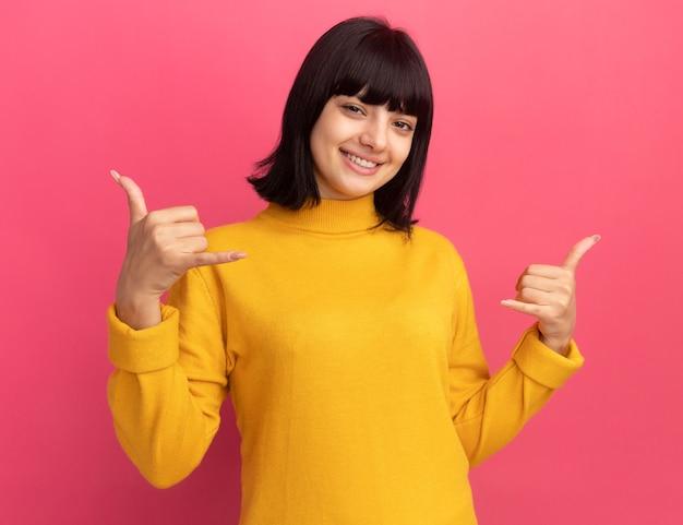 Uśmiechnięta młoda brunetka kaukaska dziewczyna robi luźny gest dwiema rękami