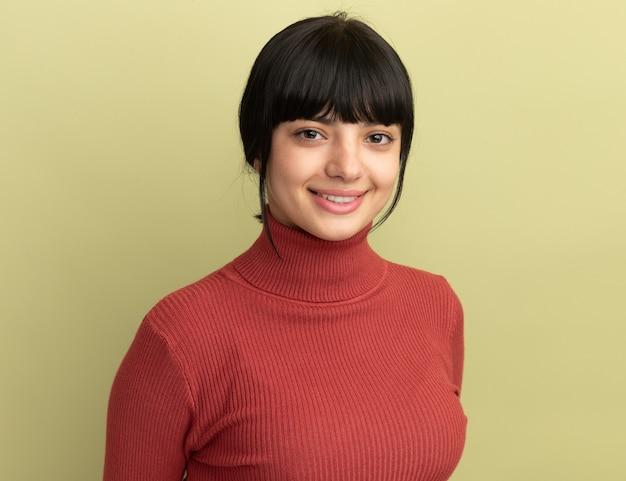 Uśmiechnięta młoda brunetka kaukaski dziewczyna patrzy na aparat na oliwkowej zieleni