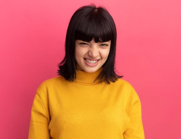 Uśmiechnięta młoda brunetka kaukaski dziewczyna stoi na różowo