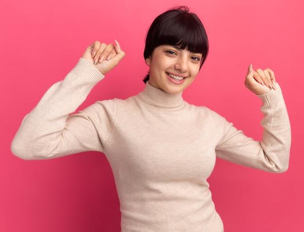 Uśmiechnięta młoda brunetka kaukaski dziewczyna stoi z podniesionymi pięściami na różowo