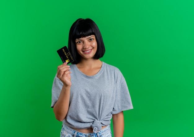 Uśmiechnięta młoda brunetka kaukaski dziewczyna trzyma kartę kredytową