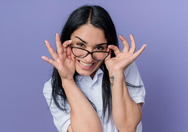 Uśmiechnięta młoda brunetka kaukaski dziewczyna trzyma okulary optyczne patrząc na białym tle na fioletowej ścianie