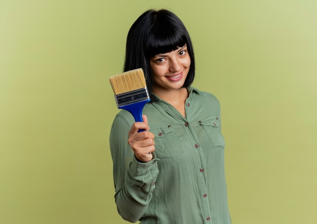 Uśmiechnięta młoda brunetka kaukaski dziewczyna trzyma pędzel patrząc na kamery na białym tle na oliwkowym tle z miejsca kopiowania