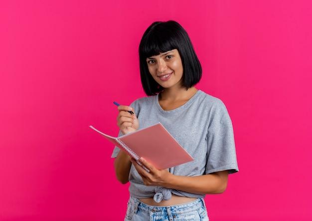Uśmiechnięta młoda brunetka kaukaski dziewczyna trzyma pióro i notatnik i wygląda
