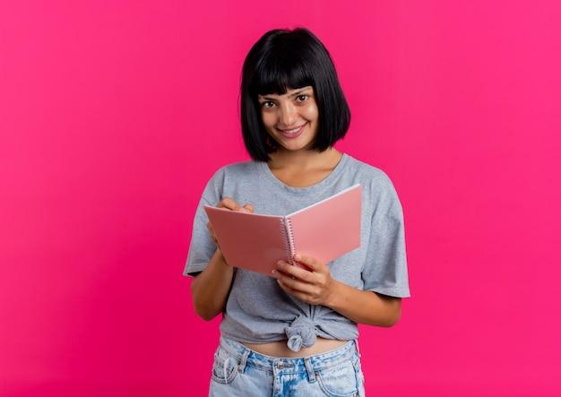 Uśmiechnięta młoda brunetka kaukaski dziewczyna trzyma pióro i szukam notebooka