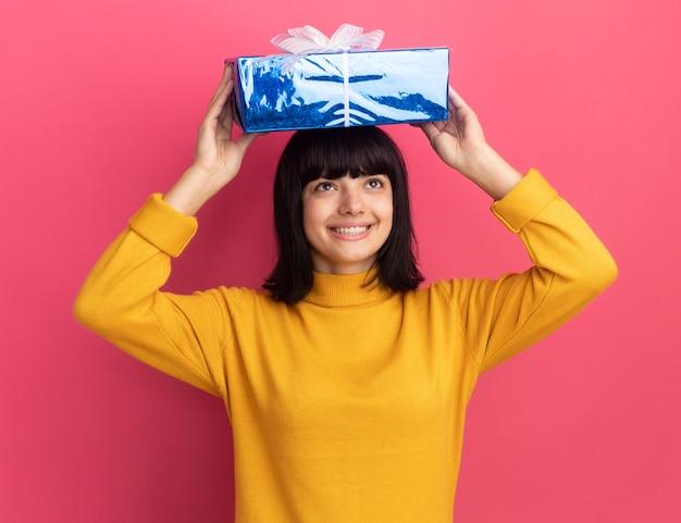 Uśmiechnięta młoda brunetka kaukaski dziewczyna trzyma pudełko nad głową na różowo