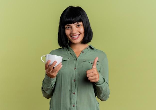 Uśmiechnięta młoda brunetka kaukaski kobieta trzyma kubek i kciuki do góry na białym tle na oliwkowozielonym tle z miejsca na kopię