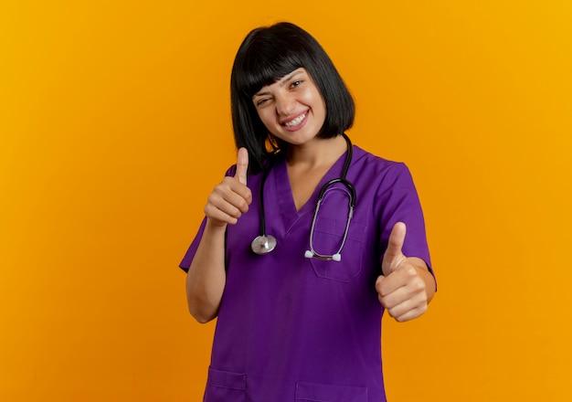 Uśmiechnięta młoda brunetka kobieta lekarz w mundurze z kciuki do góry stetoskop obiema rękami na białym tle na pomarańczowym tle z miejsca na kopię