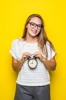 Uśmiechnięta młoda brunetka kobieta w białej koszulce pozuje na żółto