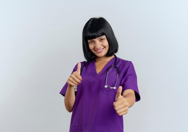 Uśmiechnięta młoda brunetka lekarka w mundurze z kciuki stetoskop obiema rękami
