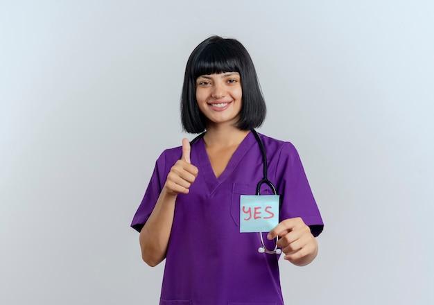 Uśmiechnięta młoda brunetka lekarka w mundurze ze stetoskopem kciuki do góry i posiada tak notatkę