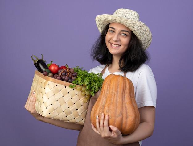 Uśmiechnięta młoda brunetka ogrodnik żeński w mundurze na sobie kapelusz ogrodniczy trzyma kosz warzyw i dyni na białym tle na fioletowej ścianie z miejsca na kopię