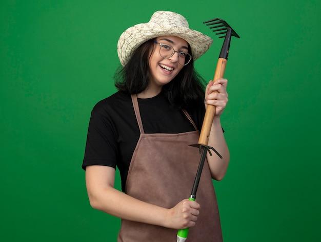 Uśmiechnięta młoda brunetka ogrodnik żeński w okularach optycznych i mundurze na sobie kapelusz ogrodniczy trzyma prowizję nad motyka grabie na białym tle na zielonej ścianie