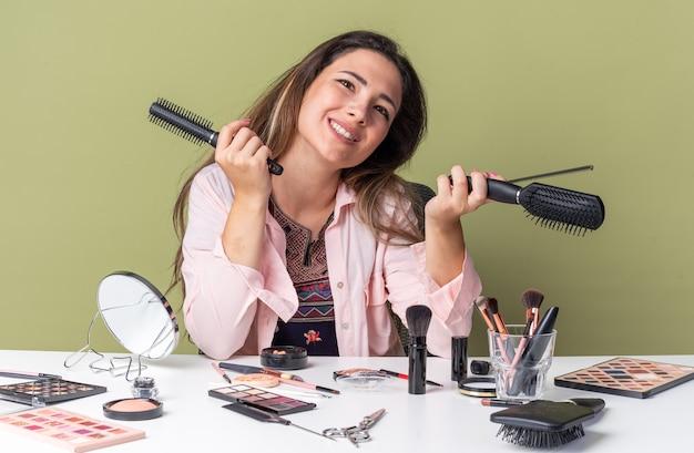 Uśmiechnięta młoda brunetka siedzi przy stole z narzędziami do makijażu, trzymając grzebienie na oliwkowozielonej ścianie z miejscem na kopię
