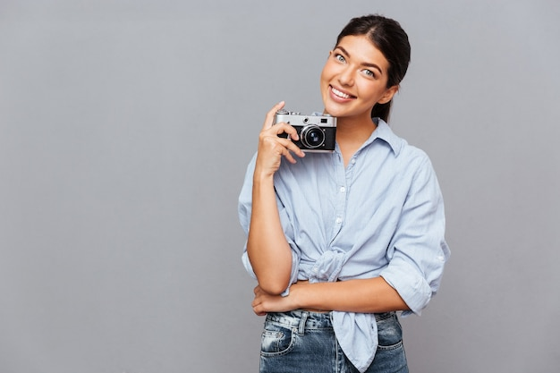 Uśmiechnięta młoda brunetka trzyma przód zdjęcia na szarej ścianie