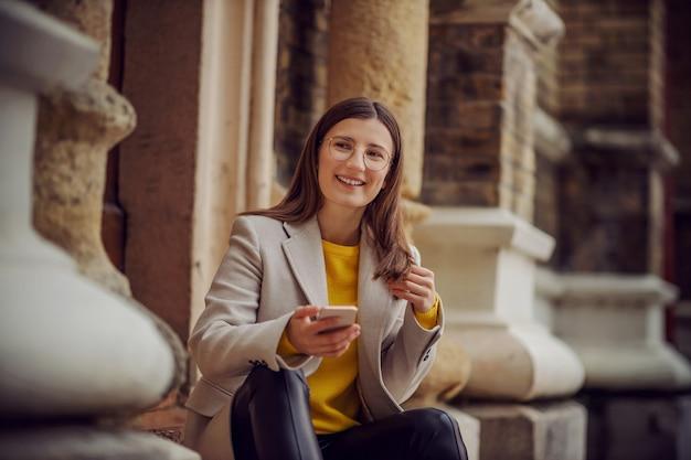 Uśmiechnięta młoda brunetka w żółtym swetrze siedzi na schodach w centrum miasta i czeka na wysłanie wiadomości