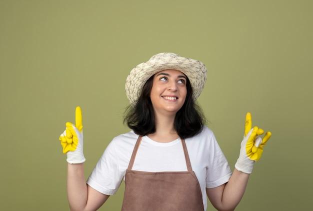 Uśmiechnięta młoda brunetka żeński ogrodnik w mundurze na sobie kapelusz ogrodniczy i rękawiczki wygląda i wskazuje na białym tle na oliwkowej ścianie