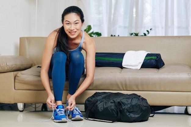 Uśmiechnięta młoda chinka zakładanie odzieży sportowej i trampki do treningu
