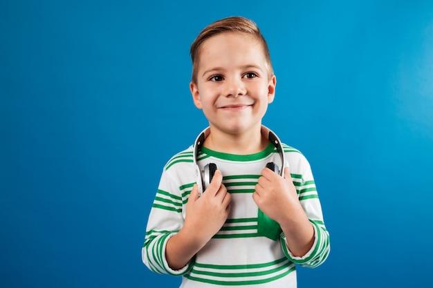 Uśmiechnięta młoda chłopiec pozuje z hełmofonem i patrzeje daleko od