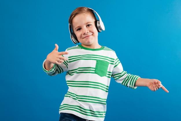 Uśmiechnięta młoda chłopiec słucha muzykę i tana