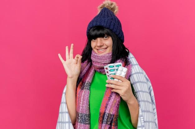 Uśmiechnięta młoda chora kobieta w czapce zimowej i szaliku owinięta w kratę trzymająca pigułki medyczne patrząc z przodu, robi znak ok na różowej ścianie z miejscem na kopię