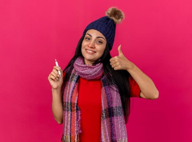 Uśmiechnięta młoda chora kobieta w czapce zimowej i szaliku trzyma termometr patrząc na przód pokazując kciuk do góry na białym tle na różowej ścianie z miejsca na kopię