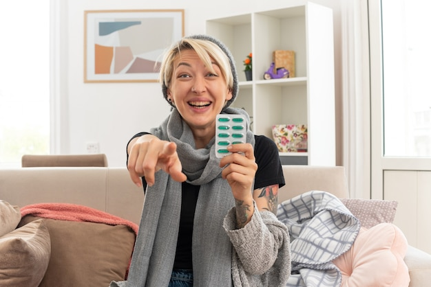 Uśmiechnięta młoda chora słowiańska kobieta z szalikiem na szyi w czapce zimowej trzymająca blistry z lekarstwami i wskazująca na przód, siedząca na kanapie w salonie