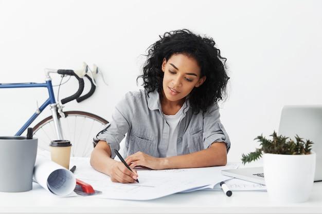Uśmiechnięta młoda, ciemnoskóra architektka pracująca na własny rachunek z fryzurą afro, rysująca
