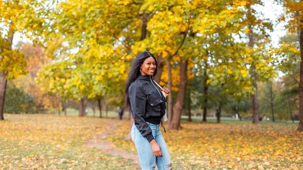Uśmiechnięta młoda czarna dziewczyna w modnych ubraniach casualowych ze stylową kurtką i dżinsami spacerująca w jesiennym parku z żółtymi jesiennymi liśćmi