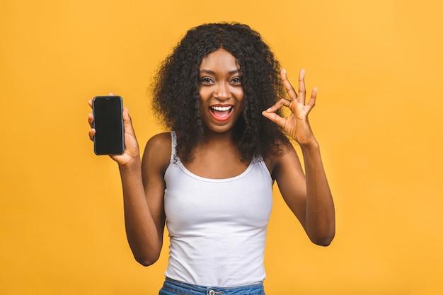 Uśmiechnięta młoda czarna kobieta afroamerykanów trzyma telefon komórkowy pusty ekran i pokazuje znak ok