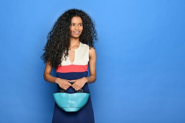 Uśmiechnięta młoda czarna kobieta w niebieskiej letniej sukience z turkusową skórzaną torebką w dłoniach, patrząc na bok