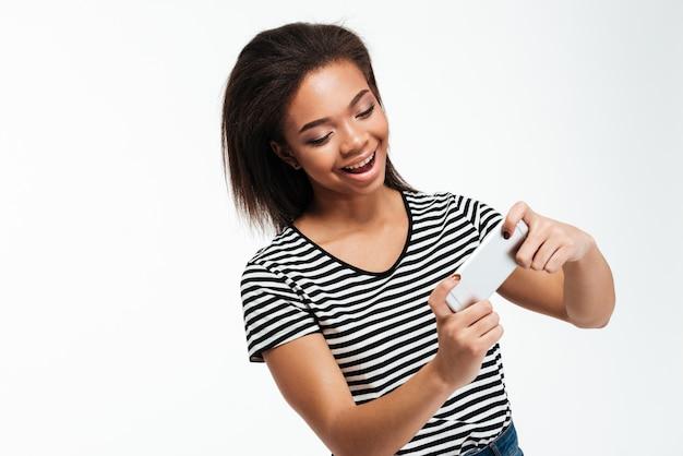 Uśmiechnięta młoda dama afrykańska grać w gry przez telefon.