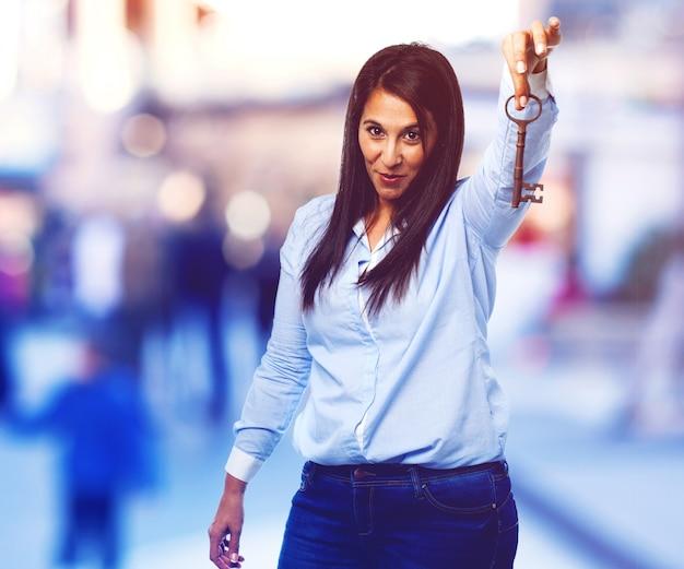 Uśmiechnięta młoda dama przedstawiający antyczny klucz