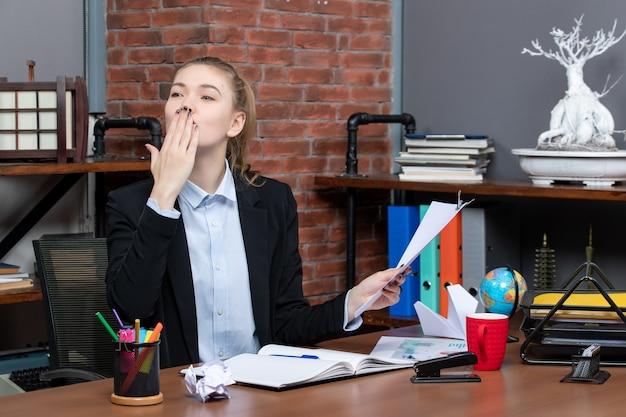 Uśmiechnięta młoda dama siedzi przy stole i trzyma dokument wysyłając buziaka w biurze