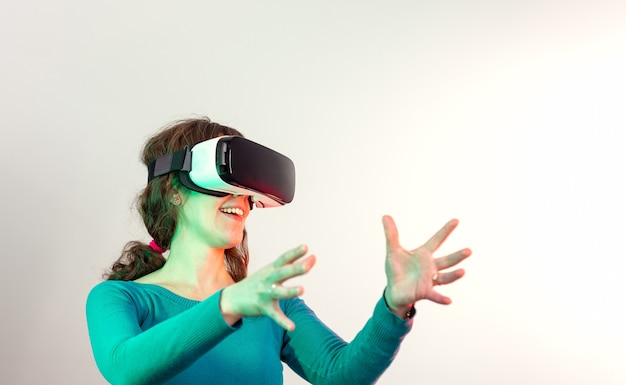 Uśmiechnięta młoda długowłosa dziewczyna w zielonym swetrze w okularach wirtualnej rzeczywistości i uniesionymi rękami na pierwszym planie patrząc w prawo, oświetlona czerwonymi i zielonymi światłami na jasnym tle