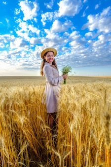 Uśmiechnięta młoda długowłosa kobieta w słomkowym kapeluszu uśmiecha się trzyma bukiet dzikich kwiatów w polu pszenicy o świcie. model patrzy bezpośrednio w kamerę, orientacja pionowa