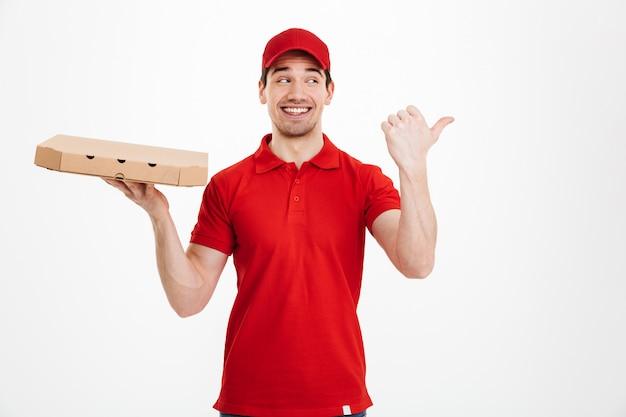 Uśmiechnięta młoda doręczeniowego mężczyzna mienia pizza.