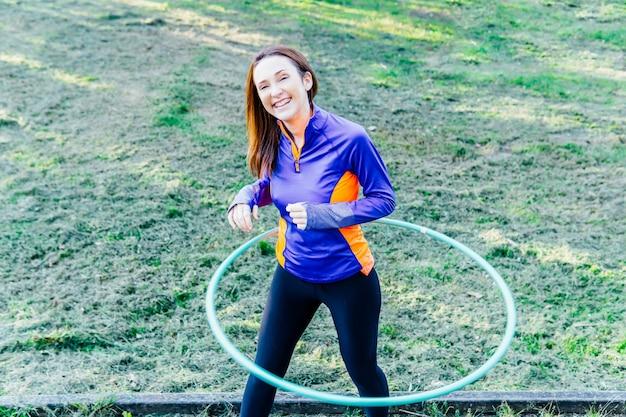 Uśmiechnięta młoda dorosła kobieta za pomocą szkolenia hula hop o zachodzie słońca. koncepcja sport park opieki osobistej weekendowe wakacje