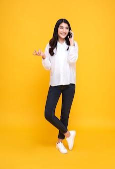 Uśmiechnięta młoda dorywczo azjatycka kobieta rozmawia inteligentny telefon na białym tle nad żółtym tłem.