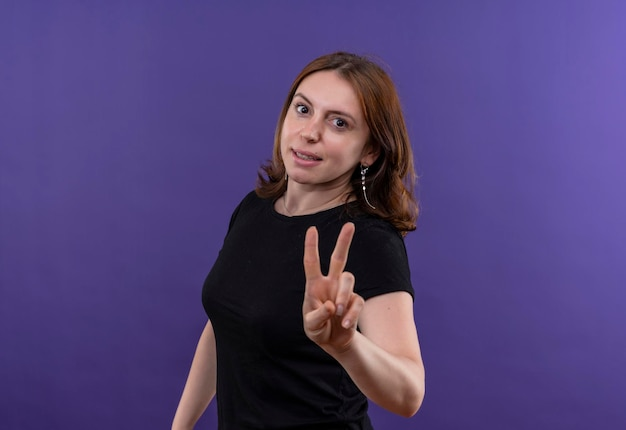 Uśmiechnięta młoda dorywczo kobieta robi znak pokoju na odosobnionej fioletowej przestrzeni z miejsca na kopię