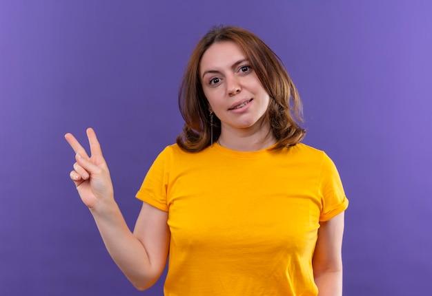 Uśmiechnięta młoda dorywczo kobieta robi znak pokoju na odosobnionej fioletowej przestrzeni
