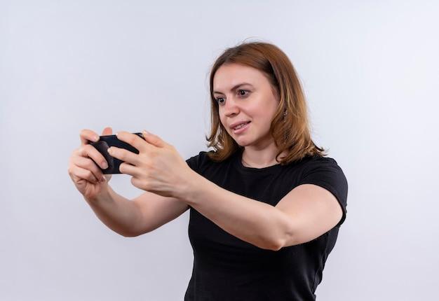 Uśmiechnięta młoda dorywczo kobieta trzyma telefon komórkowy i patrzy na niego na odosobnionej białej przestrzeni