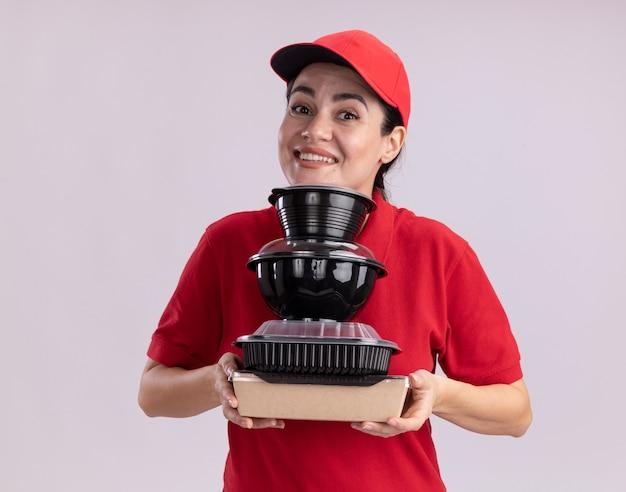 Uśmiechnięta młoda dostawa kobieta w mundurze i czapce trzymająca papierowe opakowanie żywności i pojemniki na żywność pod brodą